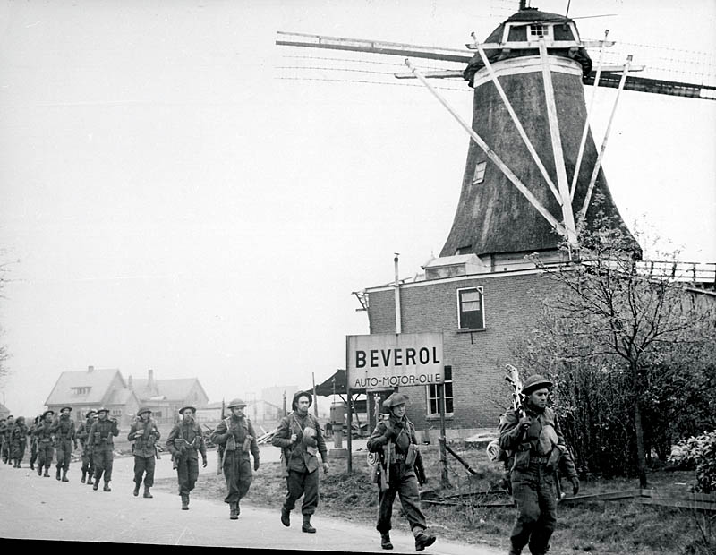 Canadian troops pass a windmill